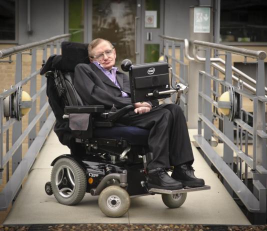 Immagine che ritrae Stephen Hawking sulla sua sedia a rotelle con sintetizzatore vocale