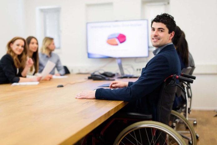 Una sala riunioni con sei persone sedute a un tavolo. In primo piano uno di loro su una sedia a rotelle.