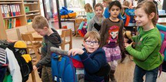 Immagine che ritrae bambini di una scuola primaria in classe, con giocattoli e zaini. Uno di loro, centrale nell'immagine, è su una sedia a rotelle con in braccio il suo zainetto