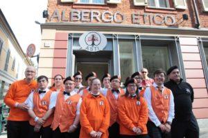 Immagine dei dipendenti dell' Albergo Etico di Asti, ragazzi con la Sindrome di Down, con indosso divisa arancione della struttura ricettiva, mentre posano davanti all'insegna dell'albergo