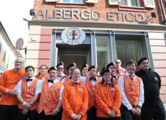 Immagine dei dipendenti dell'Albergo Etico di Asti, ragazzi con la Sindrome di Down, con indosso divisa arancione della struttura ricettiva, mentre posano davanti all'insegna dell'albergo