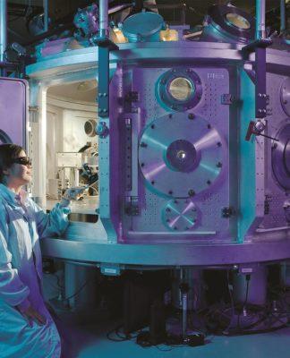 L'immagine rappresenta una giovane fisica in un laboratorio sperimentale